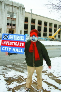 PHOTO BY CHUCK HOVEN Thursday, January 23, 2013; John Marshall High School demolition site, 3952 W. 140th Street: Wearing a gas mask, Satinder P. S. Puri stands in front of the site where cranes are demolishing the historic high school building. P.S. Puri seeks an investigation of Council President Martin Sweeney and Cleveland Mayor Frank Jackson for their complicity in orchestrating the destruction of this historic landmark.