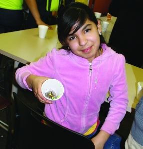 PHOTO BY CHUCK HOVEN Thursday, March 20, 2014, Fulton Branch, Cleveland Public Library, 3545 Fulton Road: Students from afterschool program of The Salvation Army's Ohio City branch participate in a science program taught by staff of the OSU Extension Service. Jecely Torres, age 12, proudly shows a plant she grew from a seed that is now just starting to sprout.