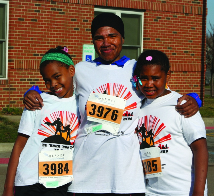 PHOTO BY CHUCK HOVEN Saturday, April 12, 2014; Be Your Own Hero 5KRace and 1 mile run, West Side Community House, W. 93rd and Lorain Avenue: Twins Rahaiila Kimolo, age 9, and Raiifa Kimolo, age 9, and Amina Abdulhaqq (center), a former West Side Community House Employee who now is a Social Worker with Catholic Charities Refugee Services. Rahaiila and Raiifa came in first and second in their age group in the one-mile run.