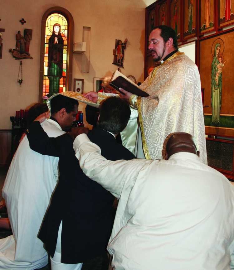PHOTO BY CHUCK HOVEN Sunday, August 3, 2014; St. Helena Romanian Byzantine Catholic Church, 1367 W. 65th Street: Fr. Petru Stanea Antwain confirms Anthony Thomas (white robe) while Godfather Jack Craciun III and Alternate Godfather Robert Weakley kneel at his side.