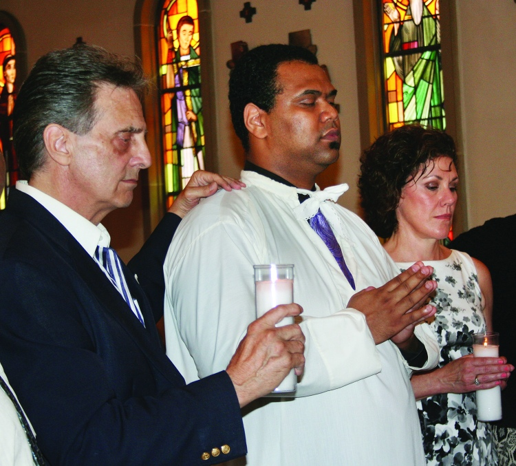 """PHOTO BY CHUCK HOVEN Sunday, August 3, 2014; St. Helena Romanian Byzantine Catholic Church, 1367 W. 65th Street: Antwain Anthony Thomas (white robe) prior to being baptized and confirmed with the name """"John"""". At the ceremony Thomas also received his first communion. Also pictured are: Godfather Jack Craciun III, Alternate Godmother Lorinda Laughlin Plank. Thomas is the first person to be baptized by Fr. Petru Stanea since his arrival as the new pastor at St. Helena Romanian Byzantine Catholic Church. He is also the first African American to be baptized at the 108 year old Byzantine Catholic Church."""