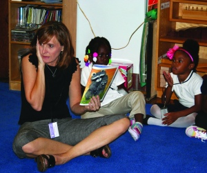 PHOTO BY DEBBIE SADLON Friday, August 22, 2014; Tremont Montessori Elementary School, 2409 W. 10th Street: Preschool teacher Ms. Susan Conrad reads to children on their first day of preschool.