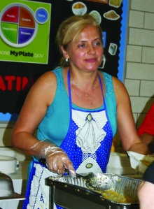 PHOTO BY CHUCK HOVEN Sunday, August 31, 2014; St. John Cantius Polish Festival, 906 College Ave: Helena Martinichin serves up kielbasa and sauerkraut to guests at the festival.