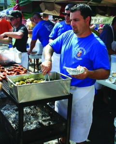 PHOTO BY CHUCK HOVEN Monday, September 1, 2014; St. Rocco Festival, 100th Year in Clark Fulton neighborhood: Paul Bellflower prepares Italian sausage for hungry festival patrons.