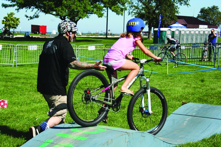 PHOTO BY DEBBIE SADLON Saturday, September 27th, 2014; Edgewater Park, Kids Zone, NEOCycle HUB event: Delaney McDaniel, age 9, of the West Boulevard neighborhood, tries out the track set up for the Kids Cruise.