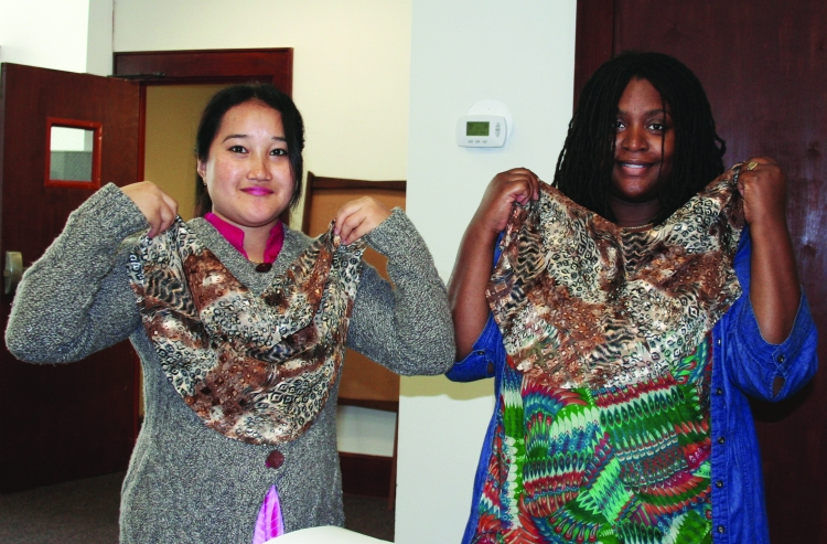 PHOTO BY CHUCK HOVEN Thursday, October 16, 2014; Esperanza Threads, 1370 W. 69th Street: (L-R) Pramila Subba and Ramona Priah hold up pieces of fabric they have cut to make into scarfs.