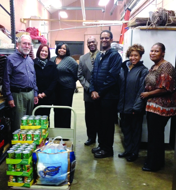 "PHOTO BY OBED W. SHELTON October 2014; La Sagrada Familia Church, 7719 Detroit Avenue: Fr. Robert Reidy of La Sagrada Familia Church (far left) accepts a money and food donation from Clerk of Courts Earle B. Turner (3rd from right), and members of the employees' committee  ""We Care"". The donation was made in the same church kitchen from which thieves stole food last June. From left to right; Fr. Robert Reidy, Marisellie Rivera (Human Resources Administrator), Shonda Jenkins (Supervisor Criminal Division), Dwight Lacey (Chief of Security) Earle B. Turner (Clerk of Courts), Delissica Crosby (Chief Deputy Clerk), and Mary Wooden (Chief Deputy Clerk)."