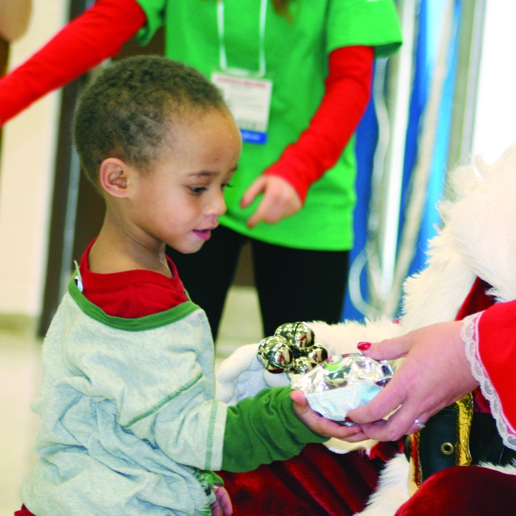 PHOTO BY CHUCK HOVEN Thursday, December 11, 2014; H. Barbara Booker School's Holiday Musical Program, 2121 W. 67th Street:  After visiting with Santa, this student accepts a gift from Mrs. Claus.