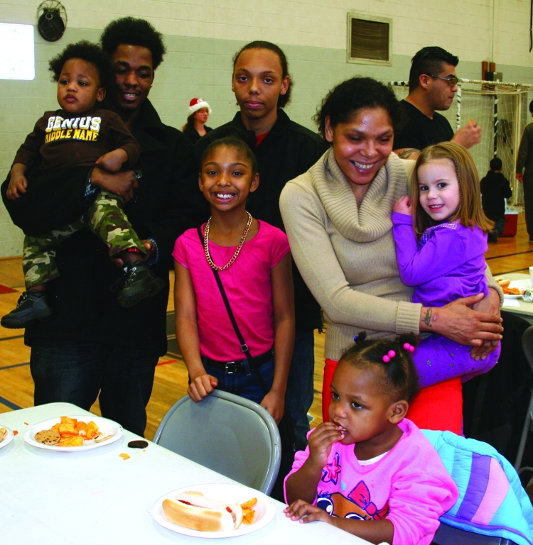 PHOTO BY DEBBIE SADLON Saturday, December 20, 2014; Zone Recreation Center Christmas Party, W. 65th and Lorain Avenue: (L-R) Top Row: SJ Burton, age 1, Stephen Burton, and Stephon Burton, Age 15. Second Row Makayla Burton, age 9, Christina Bruton and Kadence Burton age 4. Bottom seated at table: Sharonda Burton, age 2.  Christina Burton and her family are enjoying some food at the Christmas Party while awaiting the arrival of Santa Claus. Demetrius Oliver of Oliver Paralegal and Credit Restoration Services joined with Zone Recreation Center Manager Monica Lelutiu to plan the party and secure gifts for an expected 200 children.