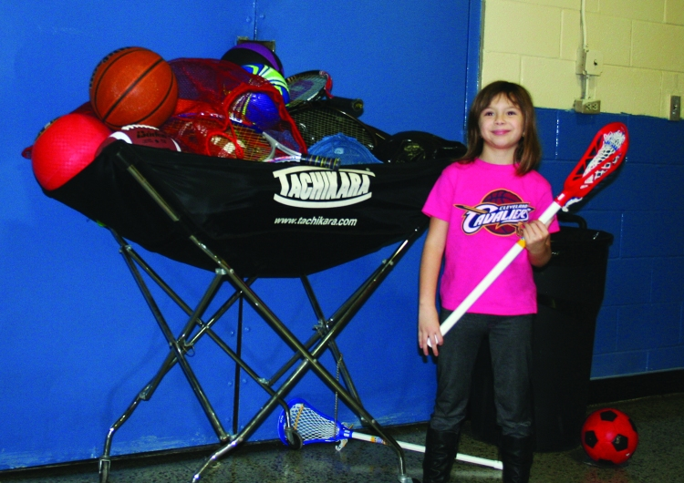 PHOTO BY CHUCK HOVEN Monday, December 8, 2014; Grand Reopening of the Hispanic UMADAOP Youth Center, 3115 Scranton Road: Izabella Hernandez, age 8, checks out the new sports equipment received by the Hispanic UMADAOP Youth Center from Keep Playing Cleveland as a result of a donation from Greg Zashin. Zashin, age 13. asked that instead of gifts at his Bar Mitzvah that donations be made to Keep Playing Cleveland.
