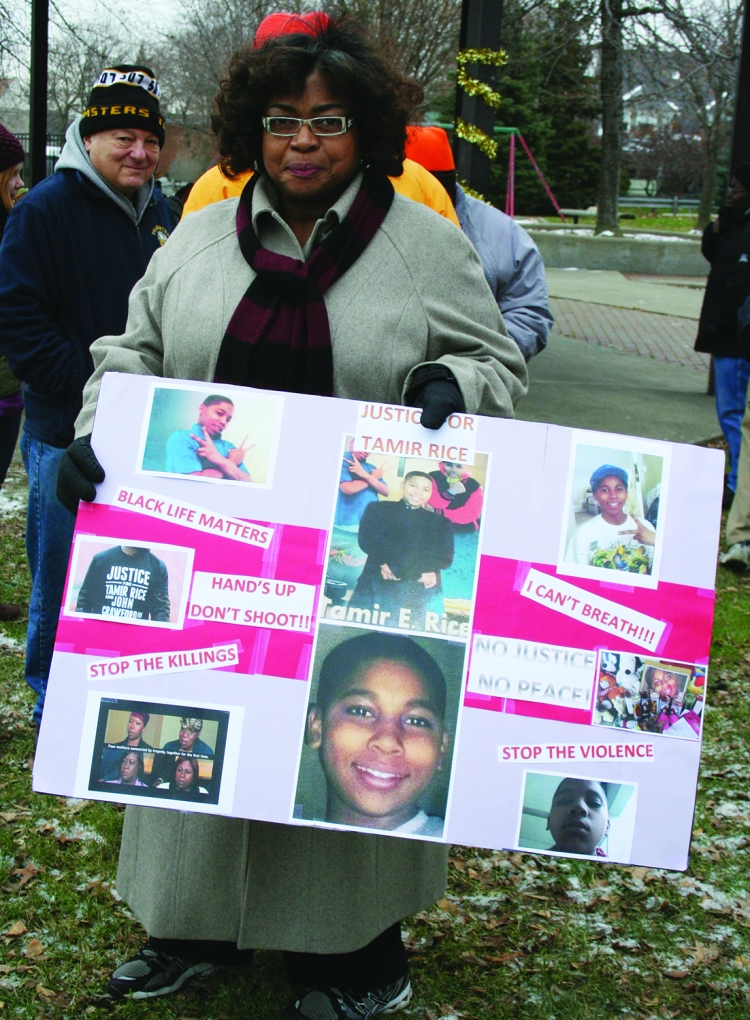 PHOTO BY DEBBIE SADLON Saturday, December 20, 2014; The Cleveland Ferguson Stance, Cudell Recreation Center, West Boulevard and Detroit Avenue: Laura Cowan holds a poster memorial to Tamir Rice, the 12 year old Cleveland boy who was shot by a police officer and killed on November 22nd near the spot where she is standing. People from Ferguson Missouri joined with Clevelanders to stand against police brutality and to honor the lives and memory of those who were killed by police. The group marched from Cudell to several West Side locations including the First Police District headquarters building. PHOTO BY HENRY SENYAK