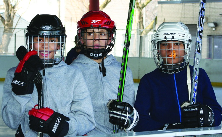 PHOTO BY DEBBIE SADLON Saturday, January 17, 2015; Halloran Park Skating Rink, 3550 W. 117th Street: Three members of the Halloran Huskies Hockey Team take time out from practice to pose for a picture.