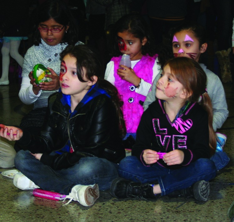 PHOTO BY CHUCK HOVEN Friday, January 9, 2015; Fiesta de Reyes (Feast of the Three Kings) celebration coordinated by the Hispanic Liaison Office of the City of Cleveland Community Relations Board, Hispanic UMADAOP Youth Center, 3115 Scranton Road: Children patiently wait as the three kings finish distributing gifts.