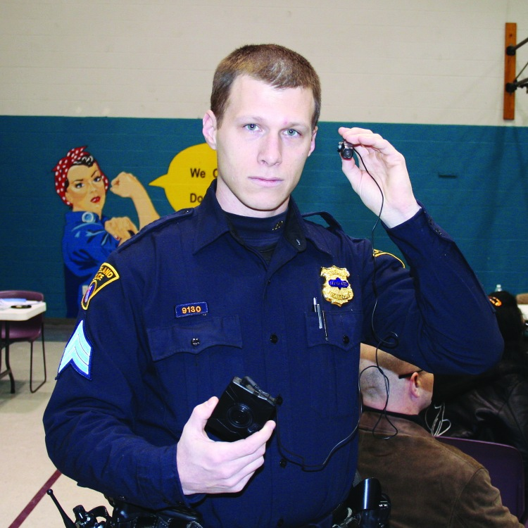 PHOTO BY CHUCK HOVEN Tuesday, February 10, 2015; Second District Community Relations Committee meeting; Applewood Center, 3518 W. 25th Street: Second District Police Officer Mitch Sheehan demonstrates the use of a clip on body-worn camera.