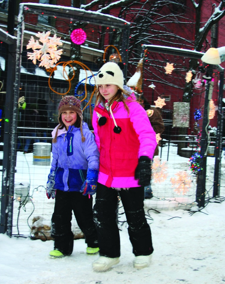 PHOTO BY CHUCK HOVEN Saturday, February 21, 2015; Brite Winter Festival, Market Street: People of all ages joined in the festivities. Here, two young girls walk past the Great Wall of Light, a creation of the Community Arts Department of the Cleveland Museum of Art.
