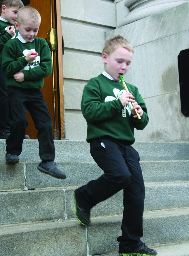 PHOTO BY DEBBIE SADLON Tuesday, March 17, 2015; St. Colman Church, 2027 W. 65th Street: A young boy plays the tin whistle as he walks down the steps of St. Colman Church after mass.