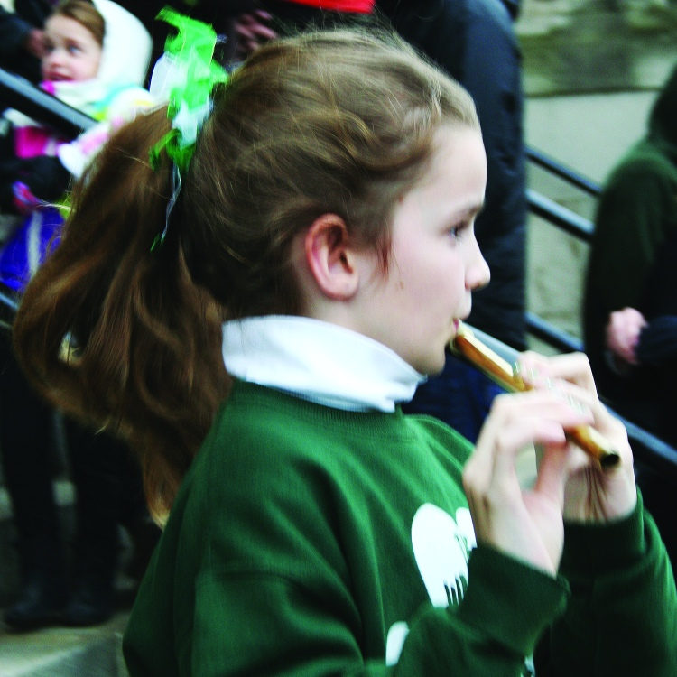 PHOTO BY DEBBIE SADLON Tuesday, March 17, 2015; St. Colman Church, 2027 W. 65th Street: A girl plays the tin whistle as she emerges from mass at St. Colman Church. West Side Irish American Club members traditionally attend mass at St. Colman Church prior to marching in the St. Patrick's Day Parade in downtown Cleveland.