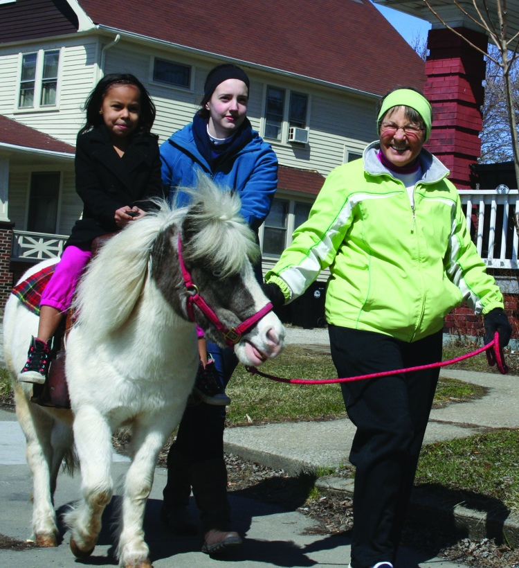 PHOTO BY CHUCK HOVEN Sunday, March 29, 2015; Palm Sunday Pony Ride, Denison Avenue United Church of Christ, 9900 Denison Avenue: Ahlivia Drdek, age 6, is on her first pony ride aboard Ariel, a pony from Coventree Farm. Susan Schnittke and Hayley Swinnerton from Coventree Farm walk along side.