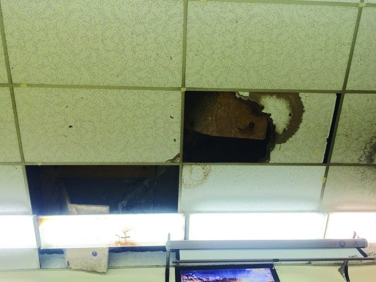 Damaged ceiling tiles in the art teacher's old room have yet to be repaired.