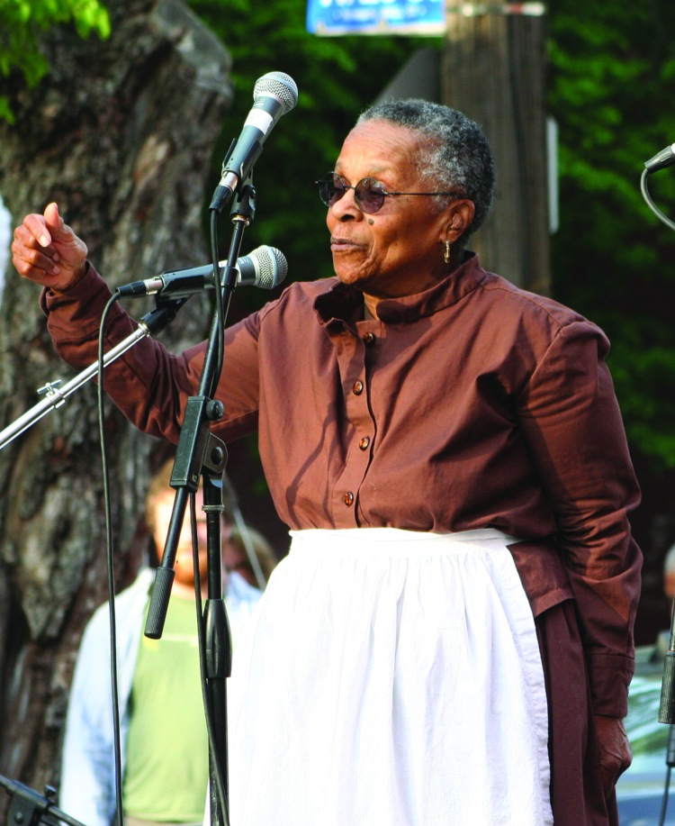 """PHOTO BY CHUCK HOVEN Saturday, May 9, 2015; Station Hope Block Party, St. John's Church, Church Avenue between W. 26 and W. 28: Joan Southgate tells the audience of the role of Cleveland, which had the code name """"Hope"""", in the Underground Railroad that """"brought freedom seekers to freedom."""" Southgate brought attention the history of the Underground Railroad by walking the 519-mile route from Ripley, Ohio to St. Catherine's Ontario in 2002 at age 73. The Underground Railroad, once traversed by Harriet Tubman and others as they guided those escaping slavery in the Southern United States, included St. John's Church among the Station Hope destinations."""
