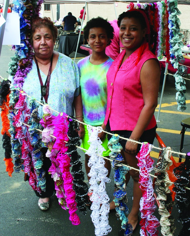 PHOTO BY DEBBIE SADLON Saturday, May 9, 2015; La Placita, monthly neighborhood open air market, US Bank Building Parking Lot, W. 25th and Clark Avenue: Carmen Nieves, assisted by her grandchildren Analese Chandler-Nieves and Jocelyn Chandler-Nieves, sells her home made scarves.