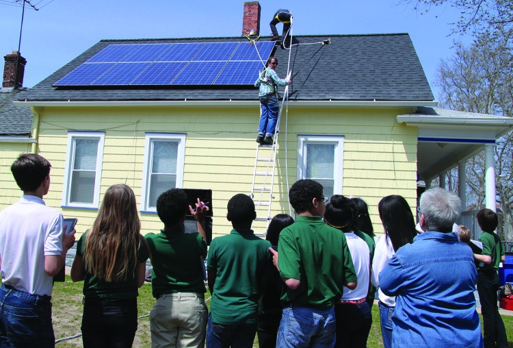 PHOTO COURTESY OF APPROPRIATELY APPLIED TECHNOLOGIES Monday, April 27, 2015; House of Champions, 2067 W. 47th Street: Urban Community School (UCS) sixth grade students from Eleanor Reagan's Science Class watch as workers from Appropriately Applied Technologies (AAT) install solar panels. AAT worked with UCS and Refugee Response to teach students about solar energy. The project included both in class instruction and real life demonstration.