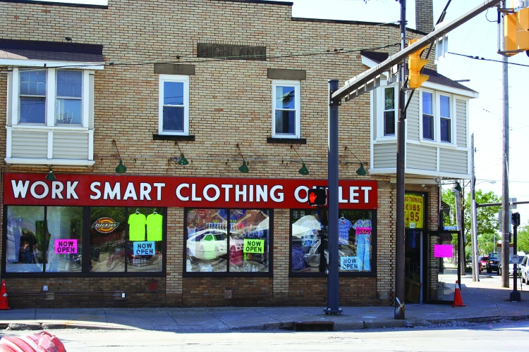 PHOTO BY DEBBIE SADLON Saturday, June 6, 2015; Work Smart Clothing Factory, 11645 Lorain Avenue: The Work Smart Clothing Store reopened in December after being closed for four months due to fire damage. Owner Nick Katsaros, age 79, says he first opened the store in 1980. He says the building originally housed a Cleveland Trust Bank and the vault is still in the building. Katsoros says the corner of W. 117th and Lorain Avenue used to be the end of the Street Car Line. As a child, he remembers his parents recalling that people would ride to the end of the line, and chose from four movie theatres to attend in the immediate area.