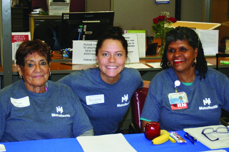 PHOTO BY DEBBIE SADLON Saturday, June 6, 2015, My MetroHealth, My Community Family Festival, MetroHealth Medical Center, corner of W. 25th and MetroHealth Drive: Volunteers Angie Garcia (Left) and Brianna Shagovac (Center) offer translation services while MetroHealth RN Teresa Simpson (Right) signs people in for free health screenings.