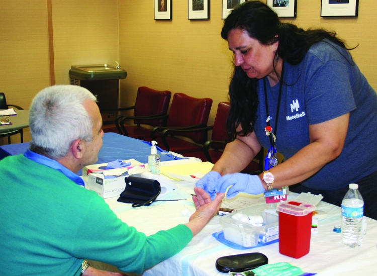 PHOTO BY DEBBIE SADLON Saturday, June 6, 2015, My MetroHealth, My Community Family Festival, MetroHealth Medical Center, corner of W. 25th and MetroHealth Drive: MetroHealth RN Mary Sanabria Simko checks the blood pressure and blood sugar level of West Side resident Ahmed Morad. Over 350 people attended the Family Festival with over 100 people taking advantage of free health screenings.