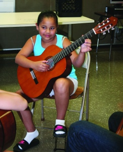 PHOTO BY DEBBIE SADLON Tuesday, July 21, 2015; Boys and Girls Club Walton School Site, 3409 Walton Ave: Jineliz Claudio demonstrates a new guitar skill to her guitar teacher, Mike McNamara, and to her sister, jomaliz Soto, who is also taking lessons.