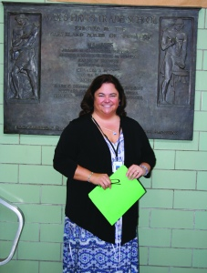 PHOTO BY DEBBIE SADLON Friday, June, 26, 2015; Max Hayes High School, 4600 Detroit Avenue: Max Hayes' new principal, Kelly Wittman, stands in front of the dedication plaque for Max Hayes High School dedicated on October 29, 1957. Wittman hopes the plaque will be moved to the new Max Hayes at W. 65th and Walworth in time for the August 17th opening of the new school year.