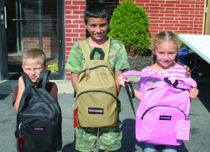 PHOTO BY DEBBIE SADLON Saturday, August 8, 2015; West 58th Street Church of God Back to School Celebration and Supply Give-A-Way, 3150 W. 58th Street: (L-R) Christopher Evcic, age 5, Cameron Evcic, age 10 and Makayla Evcic, age 6, display their new backpacks filled with school supplies.