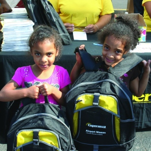 PHOTO BY DEBBIE SADLON Saturday, August 8, 2015; Esperanza, Ready to Learn, Back to School Celebration for Students, Esperanza Parking Lot, 3104 W. 25th Street: Angeli Rodriguez, age 5, and Elizabeth Rodriguez, age 4, hold up their new Esperanza backpacks filled with school supplies.