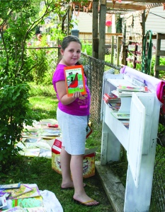 PHOTO BY DEBBIE SADLON Saturday, August 8, 2015; 20th Anniversary Celebration, Bigelow Garden Site, 3164 W. 82nd Street: Mariah Myers, age 8, stocks the garden's Little Free Library with donated books