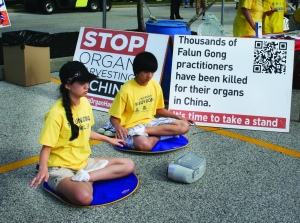 PHOTO BY DEBBIE SADLON Tuesday, August 4th, 2015; National Night Out Against Crime, Steelyard Commons: Jane Yifei Gao, Gracia Lu, and Andres Lu meditate outside a booth which urges Clevelanders to sign a petition to stop forced live organ harvesting in China. The youths meditating are practitioners of Falun Dafa (Falun Gong), a traditional Chines self-cultivation practice now banned in China.