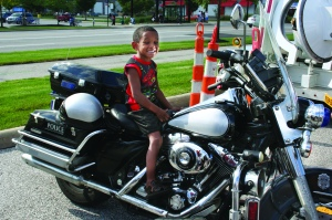 PHOTO BY DEBBIE SADLON Tuesday, August 4th, 2015; National Night Out Against Crime, Steelyard Commons: Quincy Johnson, age 5, mounts a police motorcycle.
