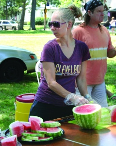 "PHOTO BY DEBBIE SADLON Sunday, August 2, 2015; ""We Care"" Expo in Jefferson Park, 13124 Lorain Ave: We Care volunteer Bartbie Chapin passes out watermelon. Walk of Faith Community Center and Aable Rents sponsored the ""We Care"" Expo, which featured food, raffles and free school supplies."