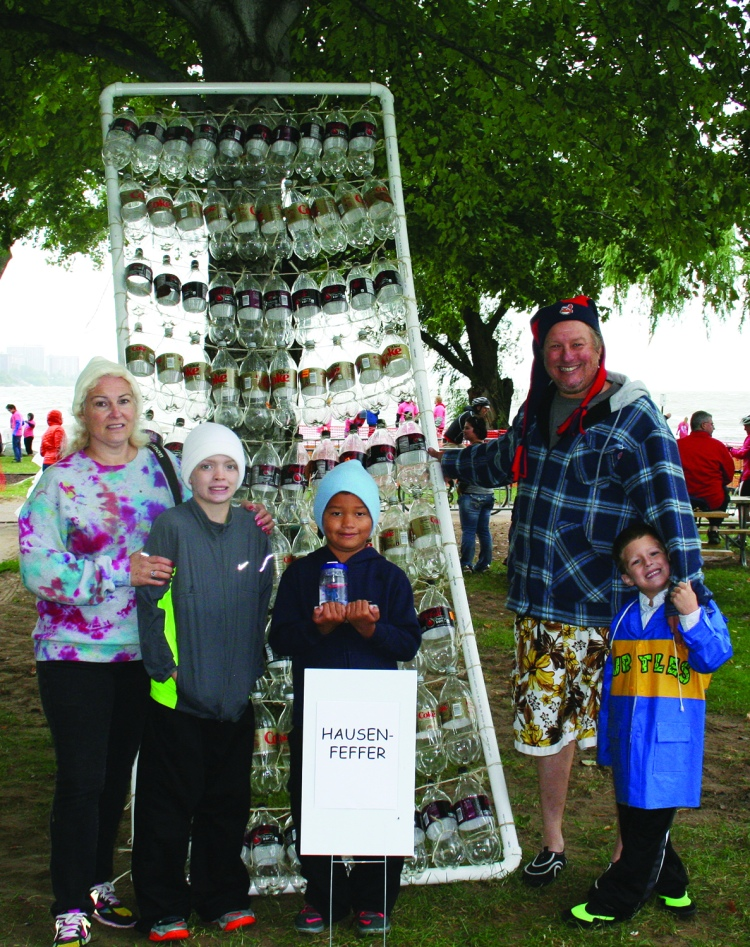 """PHOTO BY DEBBIE SADLON Saturday, September 12, 2015; Great Lake Erie Boat Float, Edgewater Park: Judges gave the award for the """"most enthusiastic"""" team to the builders of the Hausenfeffer, a craft built largely of empty plastic coke bottles. Team members are: Al Demor, Julie Demor, Joe Adams, age 10, Cameron Adams, age 7, and Colton Krafchek, age 5. The team was formed after the family attended last year's Great Lake Erie Boat Float."""