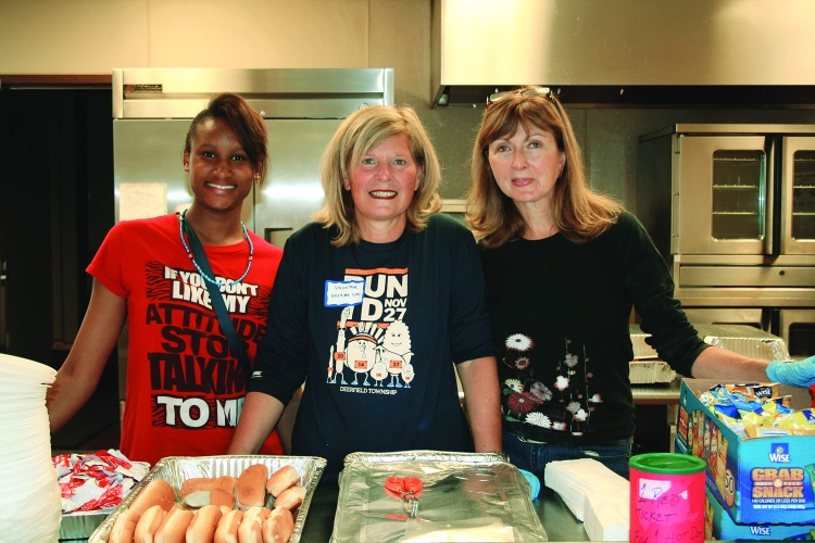 PHOTO BY DEBBIE SADLON Saturday, September 12, 2015; the Bridge Beats and Treats Festival, West Side Community House, 9300 Lorain Avenue: Volunteers (L-R) Mirakale Anthony, Karla Lux and Pennie Gray serve hot dogs to those attending the festival.