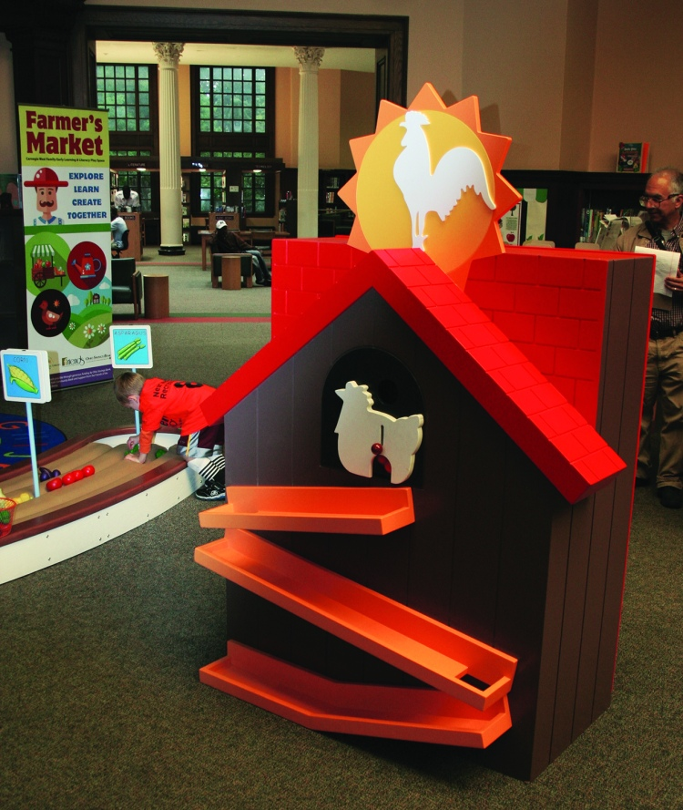 PHOTO BY DEBBIE SADLON Saturday, September 12, 2015; Carnegie West Library's Family Learning & Literacy Play Space, 1900 Fulton Road: The chicken coop is one of the farm stations where children can gather eggs and take them to the farmers market.
