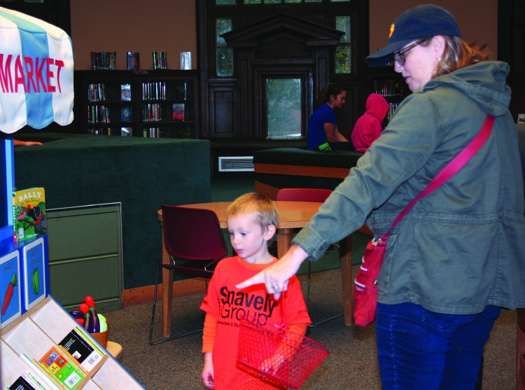 PHOTO BY DEBBIE SADLON Saturday, September 12, 2015; Carnegie West Library's Family Learning & Literacy Play Space, 1900 Fulton Road: Brooke King points out some of vegetables in the farmers' market truck to her son Oscar Fraunfelder, age 4. Oscar, spent the morning planting and harvesting the plastic vegetables in the Farmers' Market Garden and retrieving eggs from the chicken coop.