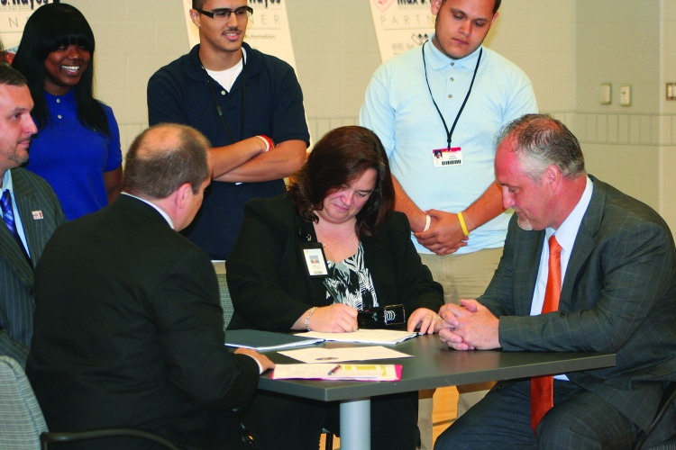 PHOTO BY DEBBIE SADLON Monday, August 31, 2015; Max S. Hayes High School Ribbon Cutting Ceremony, 2211 W. 65th Street: Max Hayes students serve as witnesses as Max Hayes Principal Kelly Wittman signs a historic agreement between the Cleveland Metropolitan School District and the Cleveland Building and Construction Trades Council outlining their collaboration in forming a pre-apprenticeship program at the school. Cleveland Metropolitan School District Chief Executive Officer Eric Gordon (left) and Cleveland Building and Trades Council Executive Secretary Dave Wondolowski (right) also signed the document.
