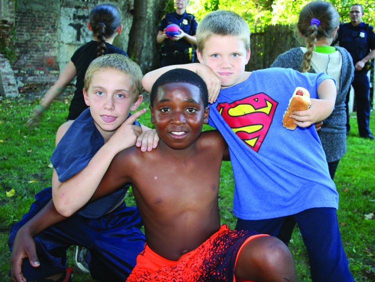 PHOTO BY CHUCK HOVEN Thursday, September 24, 2015; Stockyard Clark Fulton Brooklyn Centre Safety Committee and International Village Neighborhood Cookout with the Cops: Zachary Fiocco, age 11; Amon Tucker, age 11; and Bobby Roark, age 7; take a break from a touch football game with Second District Police Officer Hubert Kidd.