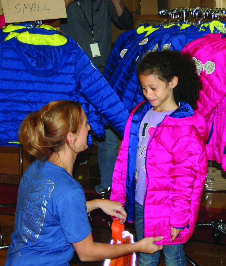PHOTO BY CHUCK HOVEN Saturday, October 17, 2015; Coat Giveaway, Thomas Jefferson International Newcomers Academy, 3145 W. 46th Street: Lindsay Pavlich, Executive Agent of Agent Outwear, passes out coats to children from the Thomas Jefferson Newcomers Academy. Pavlich says her company, based in the city of Detroit, donates one coat to charity for every coat it sells. She says Continuum Energy, a natural gas supplier, helped to sponsor the coat giveaway. The Newcomers Academy at Thomas Jefferson has many students new to Cleveland that arrived here from countries all over the world.  Many of the students have never lived in a cold climate.