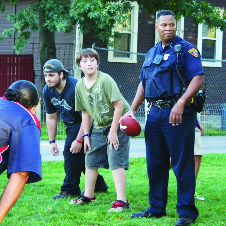 PHOTO BY CHUCK HOVEN Thursday, September 24, 2015; International Village Neighborhood's Cookout with the Cops: Second District Police Officer Hubert Kidd plays quarterback, joining neighborhood residents in a game of touch football.