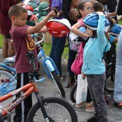 Nefty Morales, age 8, and Diana Cordero, age 5, examine their new bicycle helmets