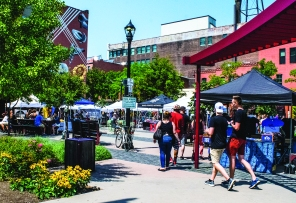 PHOTO BY MICHAEL OAKAR Saturday, August 18, 2018; Cleveland Bazaar at Market Square Park, W. 25th and Lorain Avenue: Pedestrians stroll past the booths of artists and craftspeople.